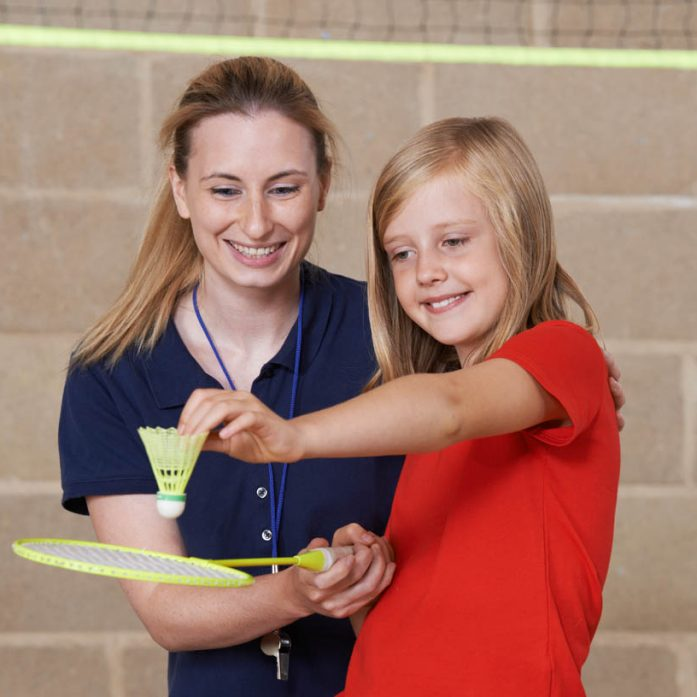Teacher Giving Female Pupil Badminton Lesson